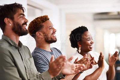 Buy stock photo Shot of a group of young creatives applauding in an office