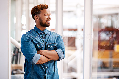 Buy stock photo Cropped shot of a handsome young male designer looking thoughtful while standing with his arms crossed in the office
