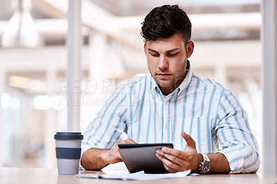 Buy stock photo Cropped shot of a handsome young male designer using his tablet while sitting in the office