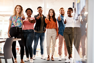 Buy stock photo Full length portrait of a group of young designers giving thumbs up to the camera while standing in the boardroom of their office