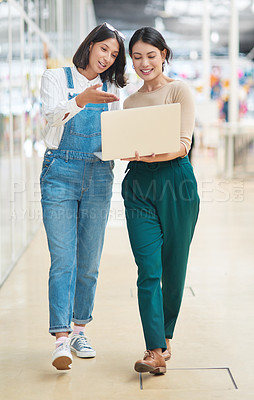 Buy stock photo Shot of two businesswomen using a laptop while walking together in an office