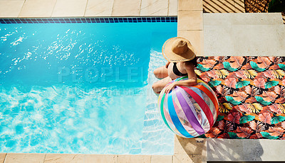 Buy stock photo Shot of a pregnant woman holding on to a beach ball while sitting by the pool