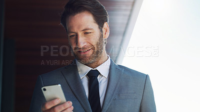 Buy stock photo Shot of a mature businessman using a cellphone outside an office