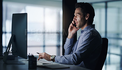 Buy stock photo Shot of a mature businessman talking on a cellphone while working on a computer in an office at night