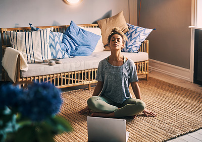 Buy stock photo Shot of a sporty young woman using a laptop while meditating at home
