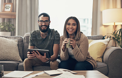 Buy stock photo Shot of a young couple sing a digital tablet while going through paperwork at home