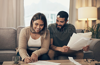 Buy stock photo Shot of a young couple going over paperwork at home