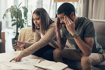 Buy stock photo Shot of a young couple looking stressed while going over paperwork at home