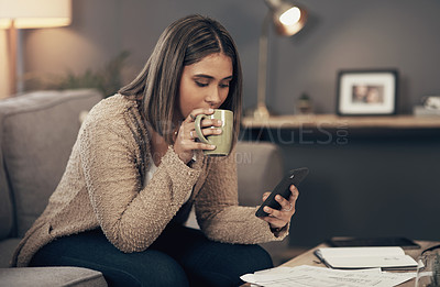 Buy stock photo Shot of a young woman having coffee and using a smartphone while going through paperwork at home