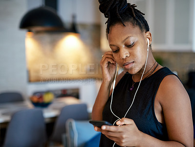 Buy stock photo Shot of a woman wearing earphones while using her cellphone at home
