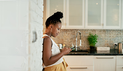 Buy stock photo Shot of a woman using her cellphone while standing in the kitchen at home