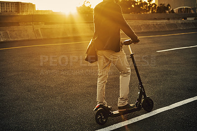 Buy stock photo Cropped shot of an unrecognizable young businessman travelling to work on his electric scooter