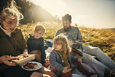 Buy stock photo Shot of a young family having lunch while sitting outdoors