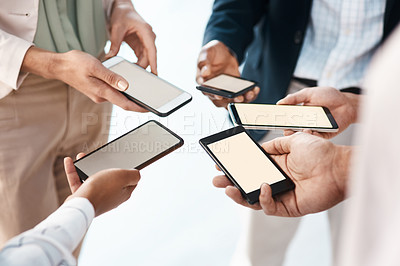 Buy stock photo Shot of a group of unrecognisable businesspeople using their smartphones together