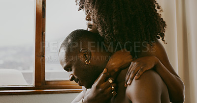 Buy stock photo Cropped shot of a young woman embracing her boyfriend while sitting at home