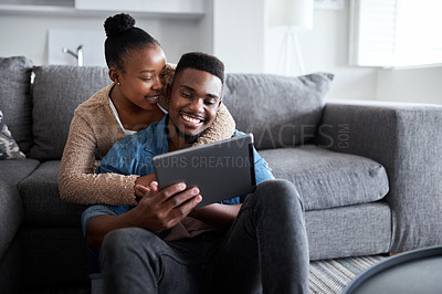 Buy stock photo Shot of a young couple using a digital tablet together while relaxing at home