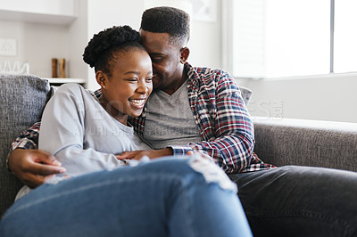 Buy stock photo Shot of a young couple relaxing on a sofa together at home