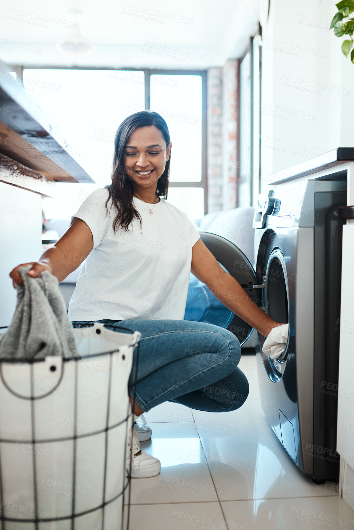 Buy stock photo Shot of a young woman using a washing machine at home