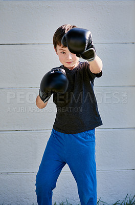 Buy stock photo Portrait of a young boy practicing a boxing routine in the garden at home