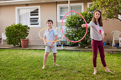 Buy stock photo Portrait of a cute young boy and girl playing with plastic hoops in the garden at home