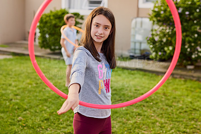 Buy stock photo Portrait of a cute young girl playing with a plastic hoop in the garden at home