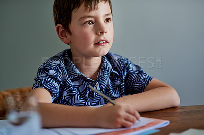 Buy stock photo Shot of an adorable little boy doing a school assignment at home