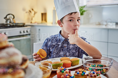 Buy stock photo Shot of an adorable little boy baking cupcakes at home