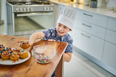 Buy stock photo Shot of an adorable little boy stealing a freshly made cupcake from the kitchen counter at home
