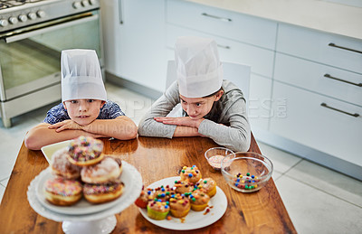 Buy stock photo Shot of an adorable little boy and girl staring at freshly baked cupcakes on the kitchen counter at home