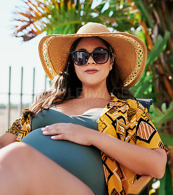 Buy stock photo Shot of a beautiful pregnant young woman spending a relaxing day by the pool