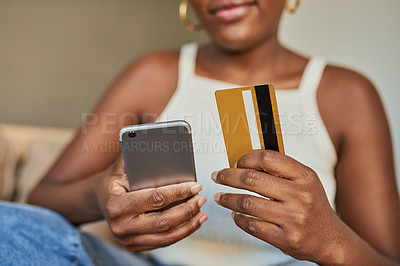 Buy stock photo Shot of a young woman using a credit card and smartphone on the sofa at home