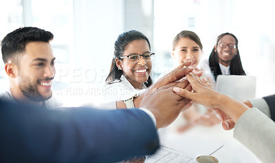 Buy stock photo Shot of a young businesswoman joining hands with her colleagues in an office