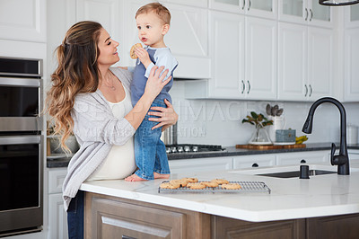 Buy stock photo Shot of a pregnant woman and her son spending time together in the kitchen at home
