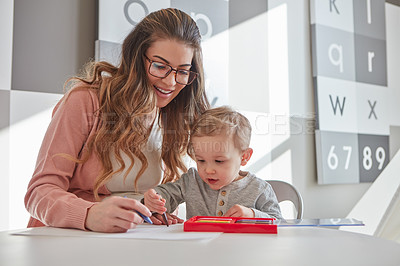 Buy stock photo Shot of a woman and her young son using crayons to draw at home