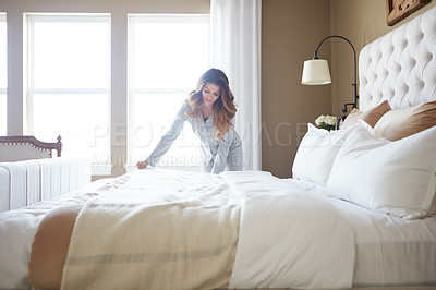 Buy stock photo Shot of a beautiful young woman making her bed in the morning at home