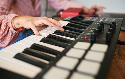 Buy stock photo Cropped shot of an unrecognizable woman playing a digital piano at home