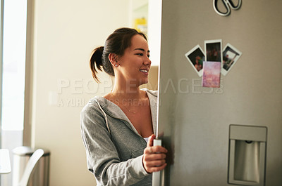 Buy stock photo Cropped shot of a young woman opening her refrigerator