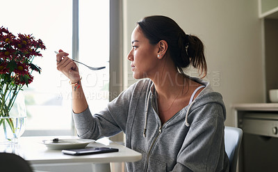 Buy stock photo Cropped shot of a woman eating breakfast while sitting at home