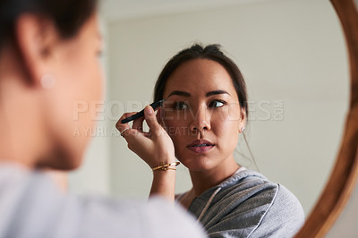 Buy stock photo Cropped shot of a woman plucking her eyebrows at home