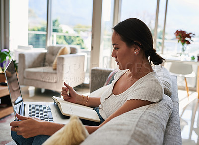 Buy stock photo Shot of a young woman making notes while sitting at home with her laptop