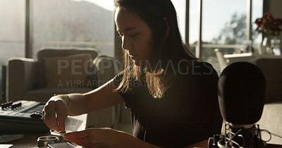 Buy stock photo Shot of a young woman preparing a marijuana cigarette at home