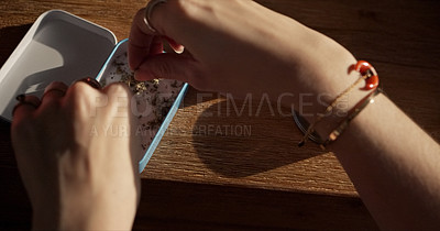 Buy stock photo Shot of an unrecognisable woman preparing a marijuana cigarette at home