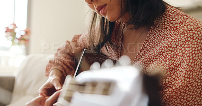 Buy stock photo Shot of an unrecognisable woman playing a guitar on the sofa at home