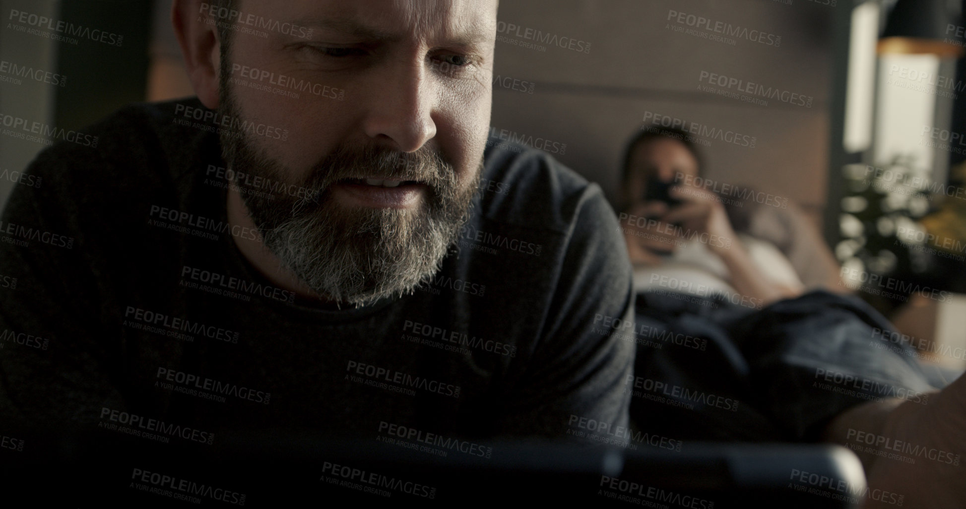 Buy stock photo Cropped shot of a handsome mature couple using their wireless devices while relaxing in bed