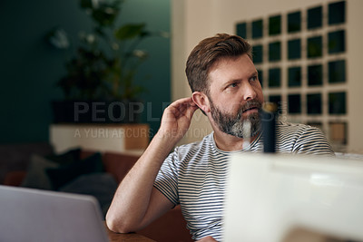 Buy stock photo Shot of a mature man using a laptop while working on a sewing project at home