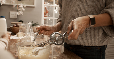 Buy stock photo Cropped shot of an unrecognisable woman busy baking at home