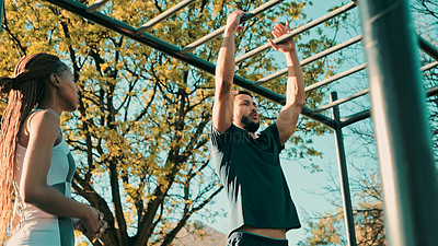 Buy stock photo Shot of a young couple using outdoor gym equipment during their workout