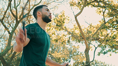 Buy stock photo Shot of a young man working out at the park with a skipping rope