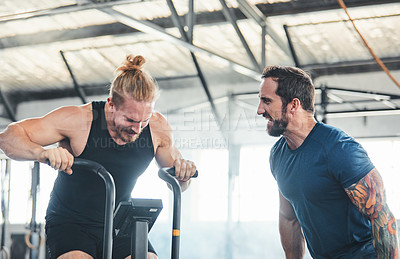 Buy stock photo Cropped shot of a handsome young male athlete working out on an exercise bike in the gym while his coach spurs him on