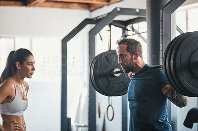 Buy stock photo Shot of a man working out with the help of his coach at the gym